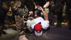 Police arrest a demonstrator protesting the killing
