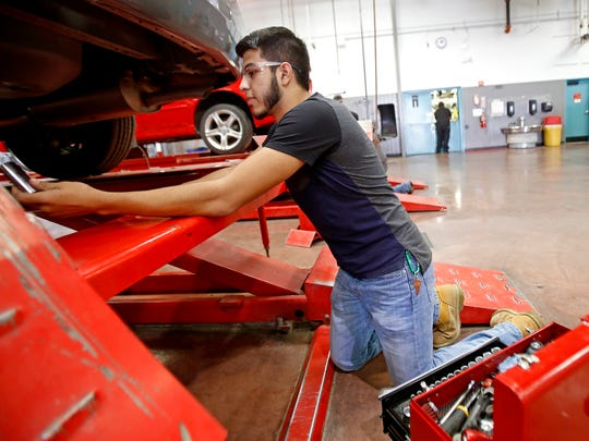 Osvaldo Acosta, 18, of Farmington, hands a tool over to a classmate on Tuesday during class in the automotive garage at the San Juan College School of Trades and Technology building in Farmington.