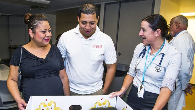 """Expectant mother Tania Carreticco, left, Phoenix, and her husband, Eduardo Felix, speak with Nurse Practioner Jennifer Allen about their """"Baby Box"""" handed out to expectant mothers for free by the Mountain Park Health Center in Phoenix. The box contains items to help a new mother take care of her newborn, including a thermometer, booties, blankets, and an umbrella for a stroller, among other items."""