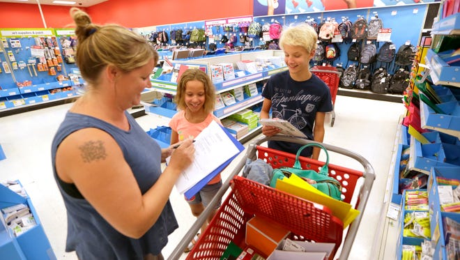 Carin Jamel of Grafton (left) and her two children, Ean (right), age 13, an eighth-grader, and Iris, age 9, a fourth-grader, look for school supplies at the Target store in Grafton.