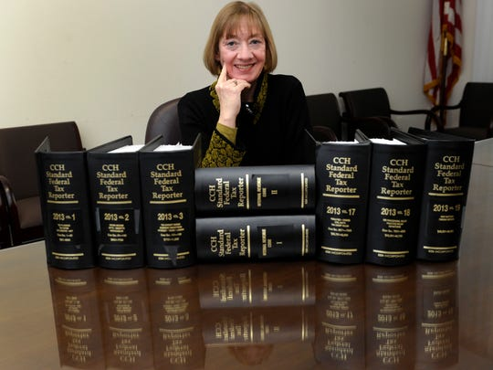 In this Thursday, Jan. 9, 2014 file photo, National Taxpayer Advocate Nina Olson poses with tax code books at the Internal Revenue Service in Washington.