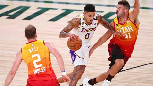 Los Angeles Lakers forward Kyle Kuzma dribbles between Utah Jazz guard Joe Ingles and forward Georges Niang during the first half of an NBA game Monday in Lake Buena Vista, Fla. Photo by Kim Klement/Associated Press