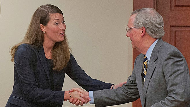 Kentucky Secretary of State Alison Lundergan Grimes shakes hands with U.S. Sen. Mitch McConnell after debating him in August 2014 in Louisville. In a race seen as key to the makeup of the Senate, out-of-state donors are pouring money into the campaigns.