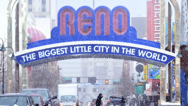 A man crosses the street in downtown Reno as a light but steady snow fall continues throw out the day on Thursday Feb. 22, 2018.