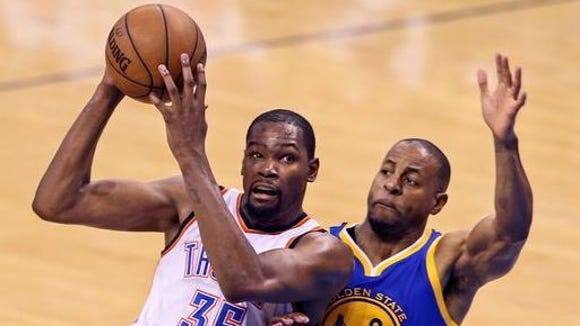 Former Oklahoma City Thunder forward Kevin Durant drives on Golden State's Andre Iguodala during this spring's playoffs. Durant announced Monday that he's agreed to sign a two-year contract with the Warriors.