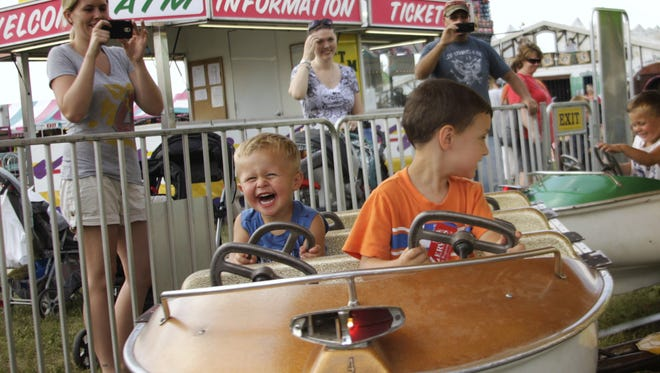 Children laugh and scream as their parents take pictures of them on a ride at a previous Sherburne County Fair.