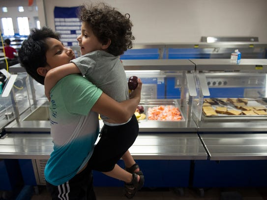 Brandon Navarro, 11, lifts his brother, Dilovan Silevani, 3, both of Nashville, while going though the food line during in a summer meals program at Whitsitt Elementary School on Tuesday, June 5, 2018, in Nashville, Tenn.