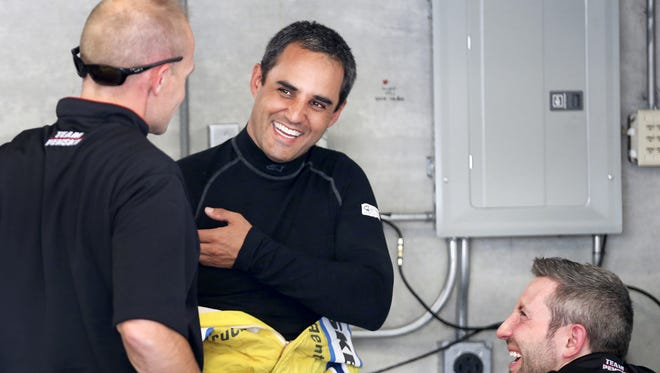 Driver Juan Pablo Montoya is all smiles as he talks with his crew in the garage area during practice in preparation for the Brickyard 400 at the Indianapolis Motor Speedway on Friday, July 25, 2014.