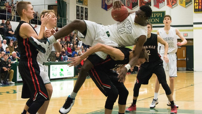 Iowa City West High's Wali Parks is fouled as he comes down with an offensive rebound during the Trojan's 77-71 victory over Linn-Mar in Iowa City. Friday, January 15, 1016. Zak Neumann freelance for Press Citizen.