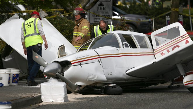 A firefighter and two Snohomosh County Airport workers look over a plane that crashed on Harbor Point Boulevard Southwest and Mukilteo Speedway, after losing power on takeoff from Paine Field on Tuesday, May 2, 2017, in Mukilteo, Wash.