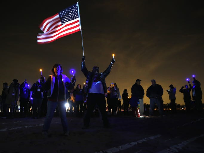 People attend a ceremony commemorating the first anniversary of Superstorm Sandy at the Light the Shore vigil on Midland Beach on Oct. 29, 2013, in Staten Island, N.Y.
