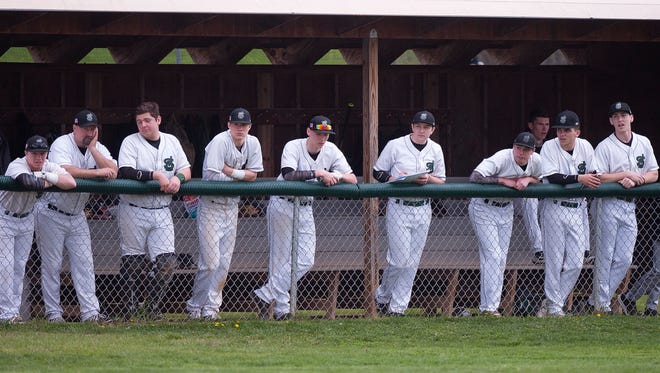 The St. Johnsbury Hilltoppers watch the action from the dugout during Saturday's high school baseball game against Champlain Valley in Hinesburg.