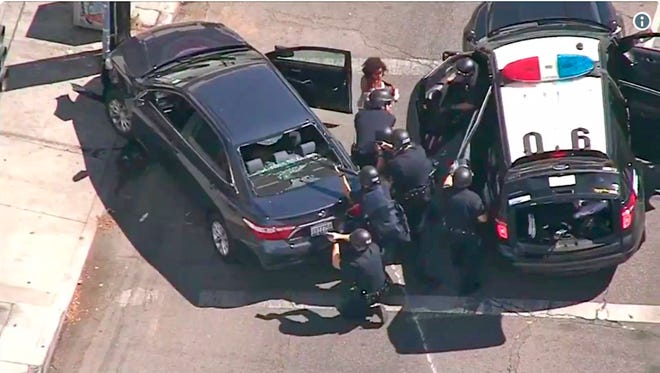 Los Angeles Police officers remove a passenger from a car that crashed after a pursuit Saturday, July 21, 2018. The driver ran into a nearby Trader Joe's grocery store in the Silver Lake district of Los Angeles and held dozens of people hostage. The manager of the store was fatally shot.