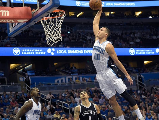 Orlando Magic forward Aaron Gordon (00) goes in for a dunk over Brooklyn Nets guard Shane Larkin (0) as Magic center Dewayne Dedmon (3) watches during the first half of an NBA basketball game in Orlando, Fla., Tuesday, March 29, 2016. (AP Photo/Phelan M. Ebenhack)