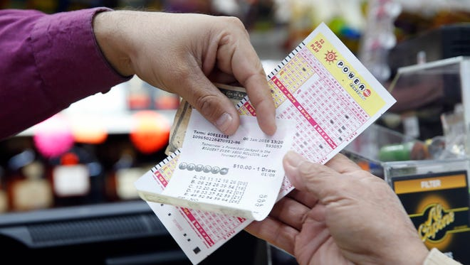 Money and Powerball tickets change hands at Pine Liquors in Fort Washington, Md., on Jan. 8 for the upcoming Powerball drawing.
