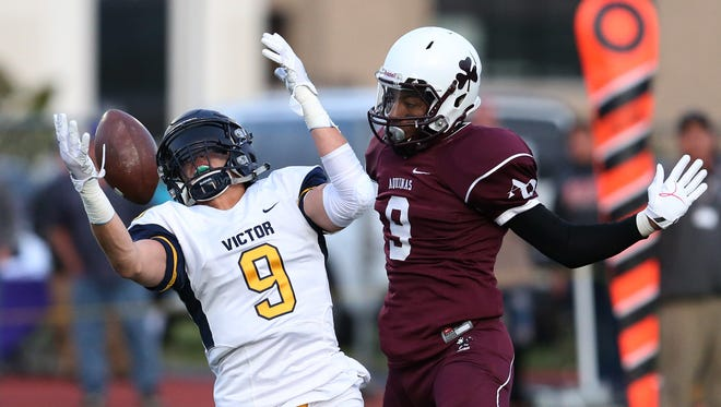 Victor's Andrew Russell, left, can't hang onto a high pass as Aquinas' Marlek Connor Jr. defends during the first half of their season opener at Aquinas Friday, Sept. 1, 2017.