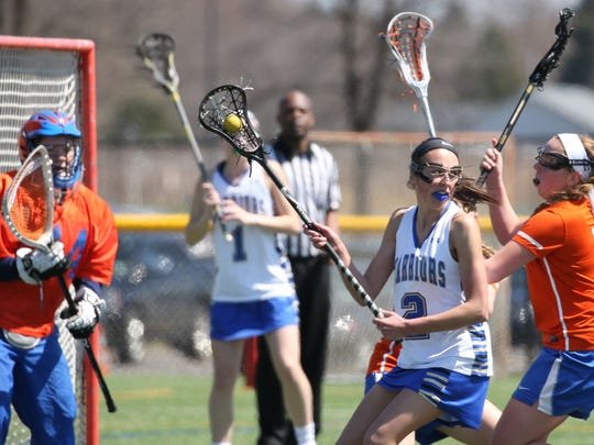 Schroeder's Payton Lill looks to pass off to a cutting teammate as she spins away from Penn Yan's Hannah Keech, right, and goalie Alexandra Cox.