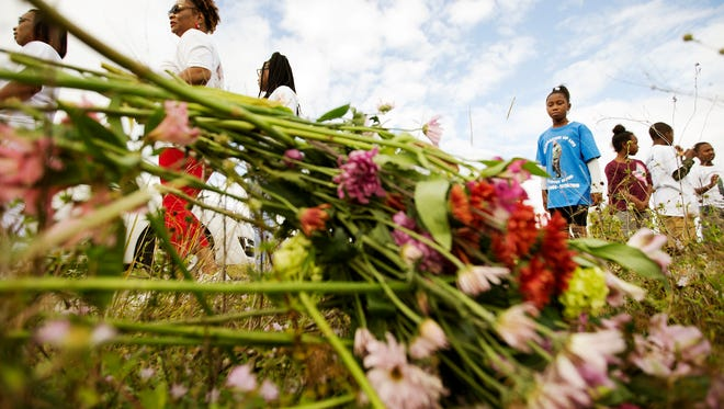 Azari Hood, 9, right, pauses at a roadside memorial honoring her father Marcus Hood on Sunday at the intersection of Estero Parkway and Cypress View Drive in Estero. Hood was killed in a shooting near the Gulf Coast Town Center on November 26, 2016. More than 50 of Hood's family and friends attended the memorial. The case remains unsolved.
