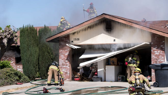 Visalia firefighters ventilate the roof of a house on fire in the 1500 block of South Crenshaw Street on Monday, April 9, 2018.