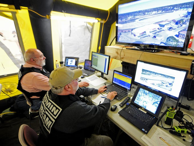 Mike Barnhart, left, and Gary House look over Google Earth while stationed inside the communications tent inside the DuPont Pavilion at the Indiana State Fairgrounds, Thursday, March 13, 2014, in Indianapolis. The Indiana Building Emergency Assessment and Monitoring (IBEAM) Team participated in a drill to test and validate plans for emergency response when building inspection must occur quickly.