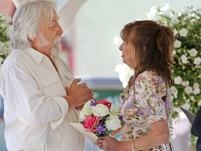 Joe Dienes, left, recites his vows as he marries Robin Everett in Markle, IN's Veteran Park, June 14, 2014.