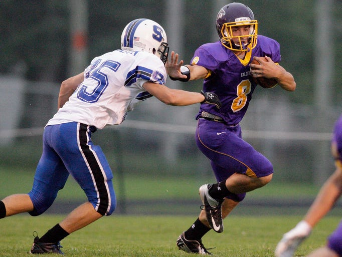 Sheboygan Falls' Beau Goudreau (8) carries the ball by a St. Mary Springs player Friday August 22, 2014 at Falls.