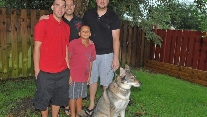 """Tony Subia and Addison Lebedz will celebrate Father's Day with their adopted sons, seen in front, Julio Ortiz-Subia, 19, and Antonio """"A.J."""" Subia, 10 -- and five foster children to whom Subia and LeBetz have opened their home. The family dog is named Takoda."""