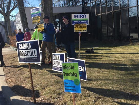 Signs supporting mayoral race candidates and supporters