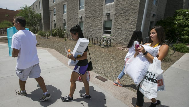 Tony Coleman (Left to right) leads his wife Claudine and daughter Taylor Coleman to Taylor's dorm, Manzanita Hall, on the ASU's Tempe campus in Tempe, AZ on August 15, 2015. The Coleman family traveled from San Antonio, Texas to move her in.