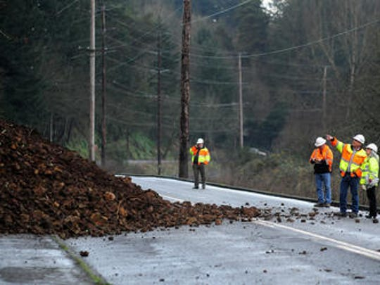 City of Salem public works employees Tena Marklin, right, and Bruce Hidebrandt examine a mudslide caused a rollover crash on River Road S on Tuesday, December 16, 2014, in Salem. The road was closed as the authorities suspected the hillside was still actively moving.