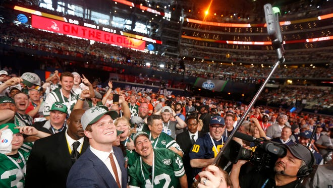 USC's Sam Darnold takes a selfie as he poses with fans after being elected by the New York Jets during the first round of the NFL football draft, Thursday, April 26, 2018, in Arlington, Texas.