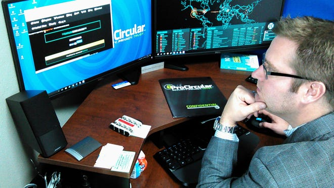 Aaron Warner of Coralville rides herd on a fast-growing cybersecurity firm he founded just this fall in North Liberty.  The world map on the right screen in his office monitors cyber attacks in real time.