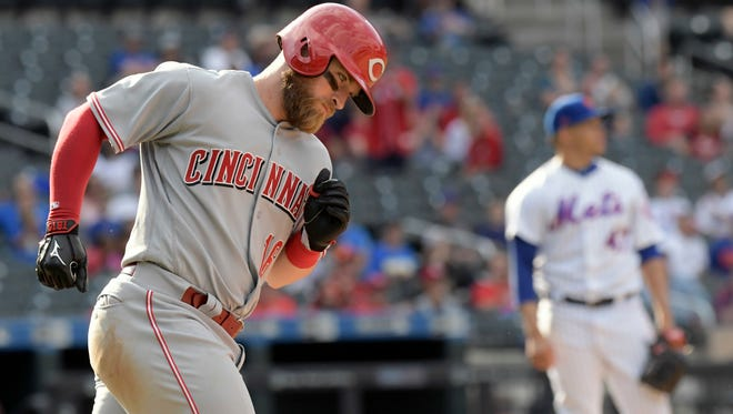 Cincinnati Reds' Tucker Barnhart rounds. the bases with a three-run home run as New York Mets pitcher Hansel Robles, right, looks on during the ninth inning of a baseball game, Sunday, Sept. 10, 2017, in New York. (AP Photo/Bill Kostroun)
