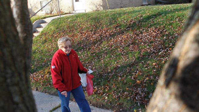 Kay Wilke walks near her home in St. Francis, carrying bags for trash and recyclables.   _______________________________