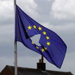 A European Union flag, with a hole cut in the middle, flies at half-staff after the historic referendum on June 24, 2016.