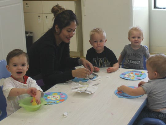 A teacher interacts with children ages 8 weeks to 5