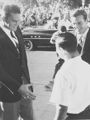 1952 Olympic gold medalist Sim Iness, left, and Bob Mathias, right, are greeted along the parade route in Tulare by Mayor Tom Drilling.
