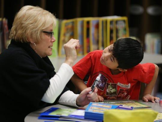 Mentor Joa Heldman keeps the attention of second grader