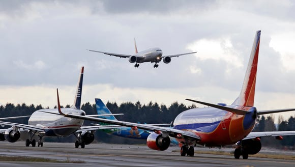 One passenger jet comes in for a landing while a line