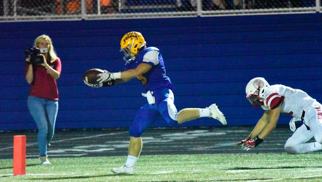 Clyde's Logan Riehl uses fancy footwork to keep his feet in bounds and stretch the ball across the goal-line for a touchdown Friday.