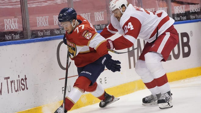 Florida Panthers center Frank Vatrano (77) and Detroit Red Wings defenseman Jon Merrill (24) battle for the puck during the second period of an NHL hockey game, Sunday, Feb. 7, 2021, in Sunrise, Fla.