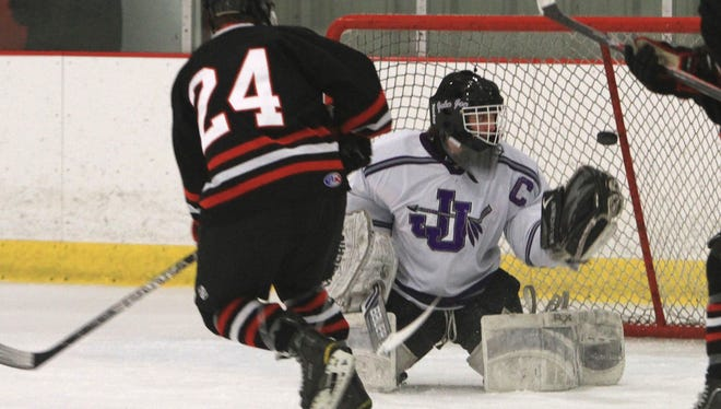 From left, Rye's Jack O'Brien (24) gets a shot by John Jay goalie Matt Lanza for a first period goal during the boys hockey Section 1 Division 2 semi-final game at the Brewster Ice Arena  Feb. 21, 2014. Rye won the game 6-3.