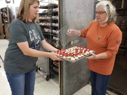 Cathey Waibel hands a tray of pumpkin cupcakes to her