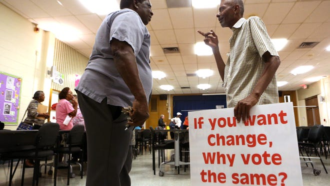 Donald Shelton (left) and Roy Hall Jr. talk following a Citizens Alliance for Fairness and Progress meeting at the Solomon Coles High School on Monday, October 17, 2016. Hall holds a campaign sign for Dr. Jimie Owsley, an at-large candidate for City Council whom spoke at the meeting.