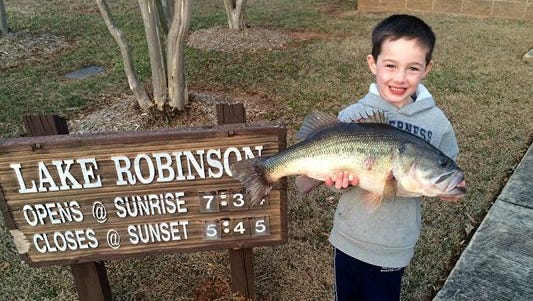 Gavin Hampton, 5, of Travelers Rest holds up the 10-pound largemouth bass he caught this past week while fishing with his father at Lake Robinson.