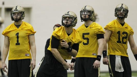 Quarterbacks Elijah Sindelar, from left, David Blough, Danny Etling and Austin Appleby watch a pass thrown by Blough during the first day of spring football practice March 10, 2015.