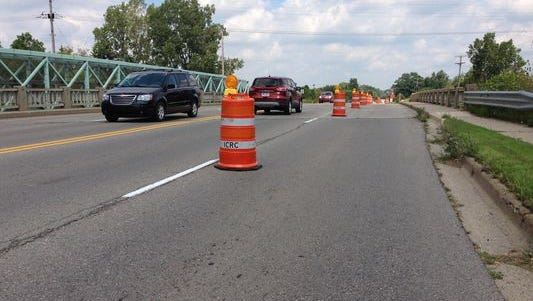 Vehicles negotiate lane closures on the Marsh Road bridge in Haslett last summer. A $1.58 million superstructure replacement project is set to begin March 21 and will close the bridge for at least a week in August.