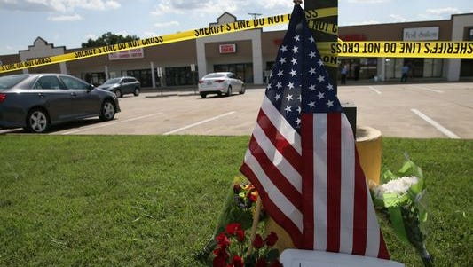 Police tape and a makeshift memorial frame the scene at an Armed Forces Career Center in Chattanooga, Tenn., where a gunman opened fire July 16, 2015, injuring a Marine.