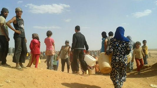 Syrian refugees gather for water at the Rukban refugee camp in Jordan's northeast border with Syria in June.