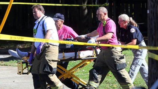 A shooting victim is taken to an ambulance at Oaklands Court PreK on Lokey Avenue Wednesday afternoon.